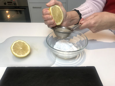Zitronensaft zum Puderzucker geben
