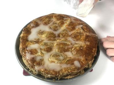 Mit einem Spritzsack die Glasur auf dem Kuchen verteilen