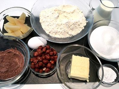 Zutaten für den Kuchen: Mehl, Schokoladenpulver, Eier, Zucker, Milch, Backpulver, Haselnüsse, Birnenkompott, Butter, Sonnenblumenöl
