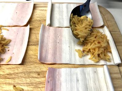 Den Reis auf die Surimi-Blätter legen und einrollen