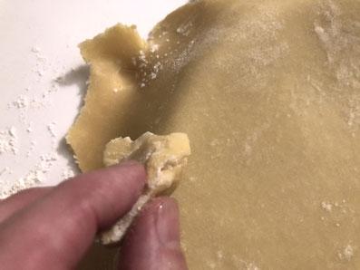 Drücke den Teig mit einem Stück Teig leicht in die Form