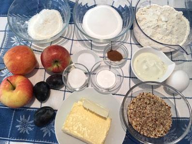 Zutaten: Mehl, Zucker, Vanillezucker, Kokosnuss, Eier, Butter, Joghurt, Salz, Backpulver, Zimt, Haselnuss, Puderzucker, Äpfel, Zwetschgen