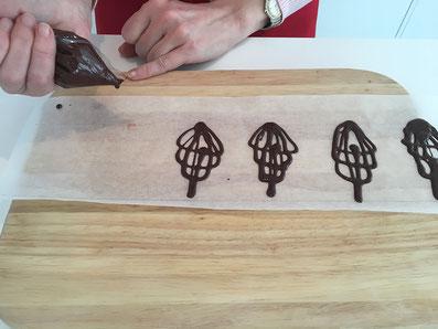 Die Schokolade in einen Spritzsack füllen und Figuren auf ein Backpapier spritzen
