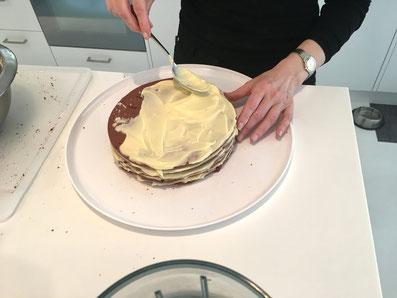 Die Tortenscheiben Schicht um Schicht mit Crème bestreichen und aufeinander legen