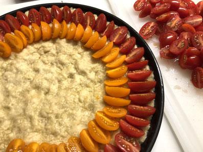 Den Teig mit den halbierten Tomaten belegen