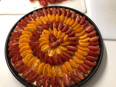 Der mit Tomaten vollständig belegte Teigboden