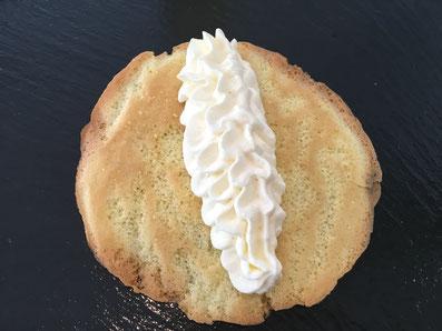 In die Mitte der Biskuitböden einen Streifen Crème spritzen