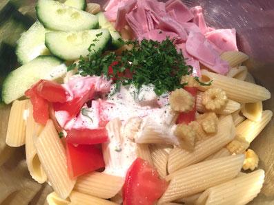 Penne, Schinken, Gemüse, Petersilie und Salatsauce in eine Schüssel geben