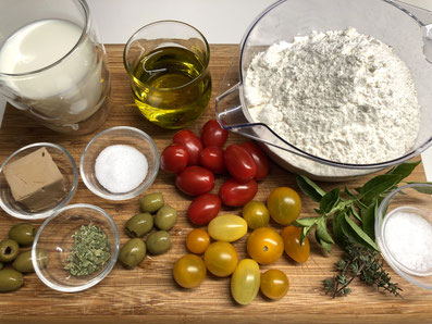Zutaten: Mehl, Milch, Hefe, Olivenöl, Salz, Cherry-Tomaten, Oliven, Ziegen-Frischkäse, Oregano, Thymian, Basilikum, Meersalz, Pfeffer