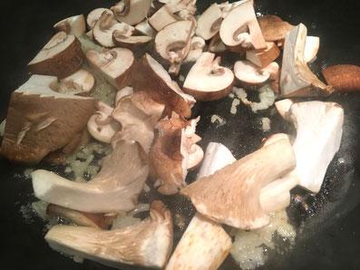 Die Pilze und die Zwiebeln in heißer Butter anschwitzen