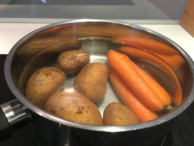 Kartoffeln und Karotten in Salzwasser blanchieren