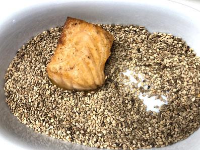 Die Honigseite in die Sesamsamen tunken