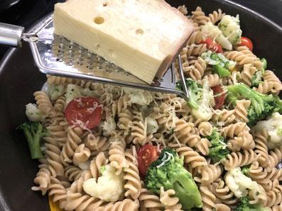 Die gekochten Fusilli untermischen und Käse darüber raffeln
