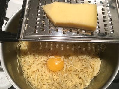 Den Vermicelli das Ei und den Reibkäse beigeben
