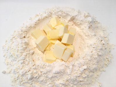 Lege die Butterwürfel in die Mitte des Mehlvulkans