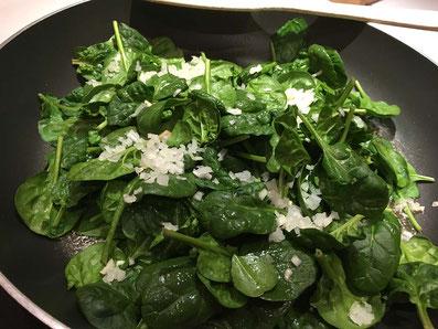 Spinat, Zwiebeln und Knoblauch in Butter schwenken