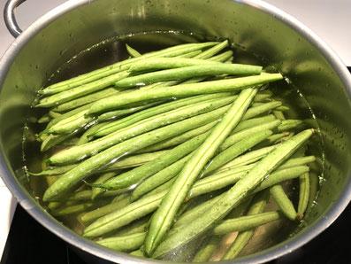 Die Bohnen in Salzwasser kochen