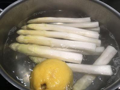 Den Spargel in Salzwasser mit einer halben Zitrone kochen