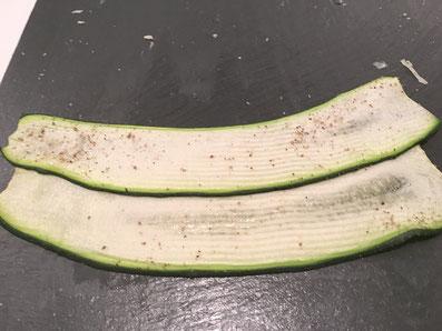 Die Zucchini-Streifen salzen und pfeffern