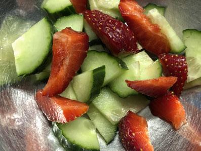 Gurkenscheiben und Erdbeeren vierteln