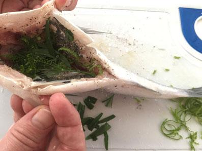 Das Innere des Fisches mit Kräuter füllen