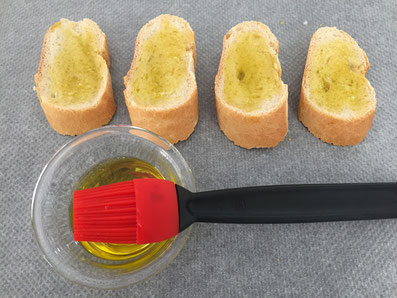Die Brotscheiben mit Olivenöl bestreichen