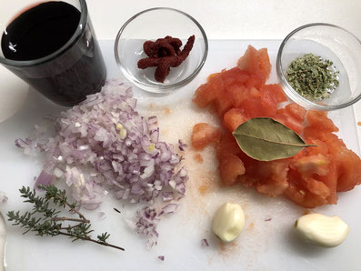 Zutaten zur Fleischmasse: Zwiebel, Knoblauchzehen, Tomatenmark, Tomaten, Thymian, Oregano, Lorbeerblatt, Rotwein, Salz, Pfeffer