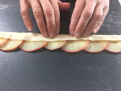 Die Apfelscheiben hälftig auf die Teig-Bahnen legen