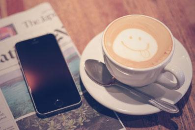 携帯電話とコーヒーの画像です。