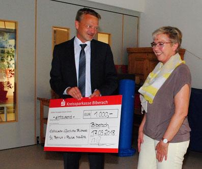 KSK-Regionaldirektor Matthias Reichelt überreicht Büchereileiterin Ingrid Reis einen Scheck in Höhe von 1000 Euro.