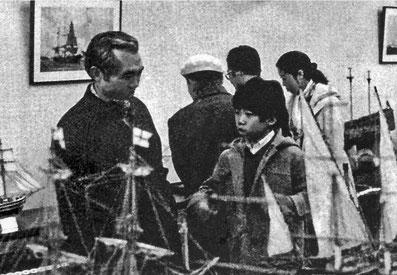 第1回展覧会場で幼かった伊藤明現社長(右)に模型の楽しさを語る伊藤恒男先代社長。40年の流れを感じる一枚だ。