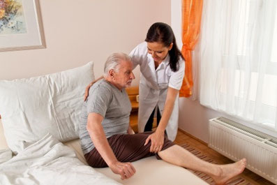 Pflegekraft aus Polen hilft älterem Herr beim zubettgehen