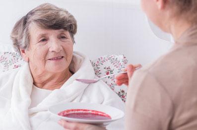 Pflegekraft aus Polen hilft ältere Dame beim essen
