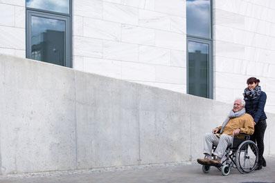 Pflegekraft aus Polen hilft älterem Herr mit Rollstuhl