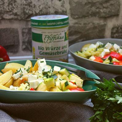 Rezept Foto Buddha Bowl mediterran, grüne Schüssel mit Kartoffel-Spalten, Zucchini und Paprika-Würfeln, Hirse und Feta, Gabel auf einer grauen Tischdecke