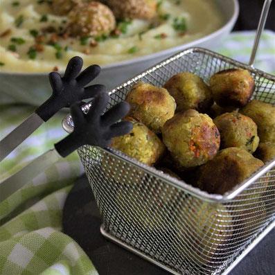 Vordergrund: kleines silbernes Frittier Sieb mit kleinen, angebratenen Klößchen, im Hintergrund: grauer Teller mit heller Suppe und Klößchen auf einer grünen Tischdecke. Rezeptfoto 1