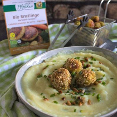 Vordergrund: kleines silbernes Frittier Sieb mit kleinen, angebratenen Klößchen, im Hintergrund: grauer Teller mit heller Suppe und Klößchen auf einer grünen Tischdecke. Rezeptfoto 2