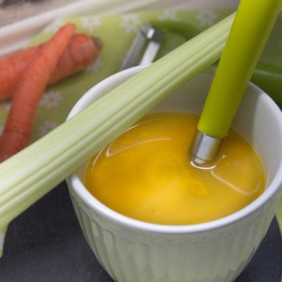 weiße Tasse mit gelber Flüssigkeit, einem grünen Löffel. steht auf einer Schieferplatte. Im Hintergrund liegen Möhren. Über die Tasse liegt eine Stange Sellerie.