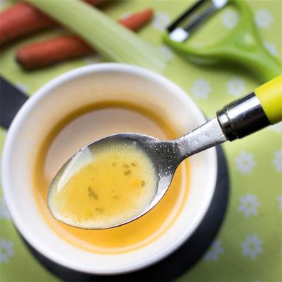 kleiner Löffel mit gelber Flüssigkeit schwebt über einer weißen Tasse mit gelber Flüssigkeit. Im Hintergrund Möhren und Stangensellerie und eine grüne Tischdecke.