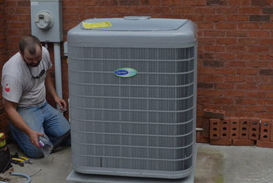 Technician installing a new Carrier air conditioner