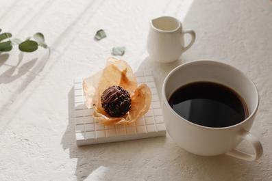 ノートパソコンの傍らにオレンジが鮮やかなガーベラのアレンジメント。カフェオレの入った赤のマグカップ。