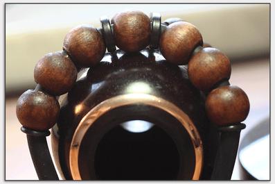 Die Holzkugeln verhindern eine direkte Berührung des Gummis am Becher um die Resonanz nicht zu stören.