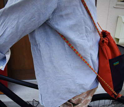 テツオミシンのナップサックを背負って自転車に乗っている写真