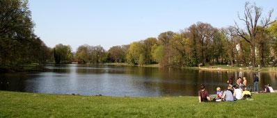 Menschen sitzen im Gras am Ufer Karpfenteich Schlosspark Charlottenburg. Foto: Helga Karl am 10.April 2009