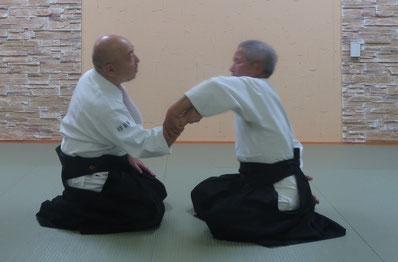 ②呼気で肘を膝の上で弛緩屈曲、手背の緊張伸展感を取って掌を包むと手首は伸展している。脇は半角の開きを保つからここでは体軸が右前に振れる。
