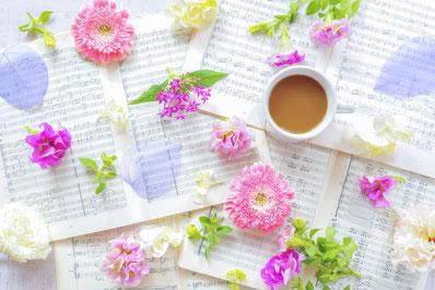 何枚も広げられた楽譜。そのうえに無造作に置かれた春の花。コーヒーの入ったマグカップ。