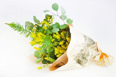 レースのテーブルクロスのうえに広げられたテキスト。ハーブティーの入った耐熱ガラスのカップ&ソーサ。菜の花が一輪。