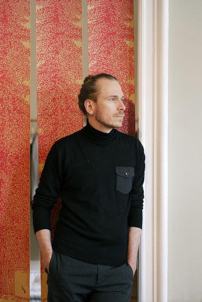 Frank Leder vor einem Vorhang aus... Leder.