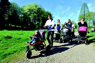 Eine Gruppe von Müttern mit ihren Babys im Kinderwagen. Gemeinsam laufen sie durch die Natur.