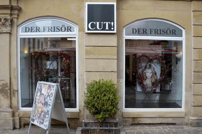 """Aussenansicht der Schaufenster des Friseursalons """"CUT! Der Frisör"""" in Winnenden."""